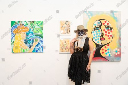 Stock Image of Artist Tatiana Lisovskaya poses with her work. One Art Space in Tribeca held an opening reception for their 5th Annual International Women's Day Art Fair. The exhibition features a diverse, international collection of talent, female-identifying artists of varying ages.