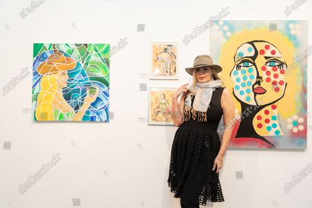 Stock Picture of Artist Tatiana Lisovskaya poses with her work. One Art Space in Tribeca held an opening reception for their 5th Annual International Women's Day Art Fair. The exhibition features a diverse, international collection of talent, female-identifying artists of varying ages.