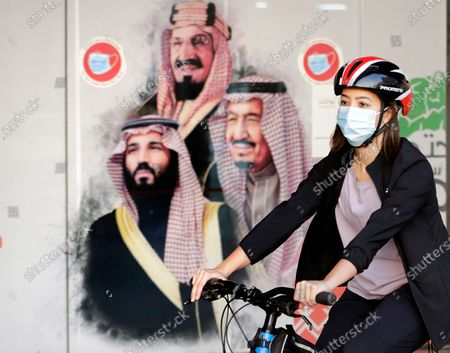 Sawsan Abdel Fattah, a Saudi cyclist member of women's brave cyclist team, rides her bicycle in front of a banner showing Saudi King Salman, right, his Crown Prince Mohammed bin Salman, left, and Saudi Arabia's founder late King Abdul Aziz Al Saud in Jiddah, Saudi Arabia . The brave cyclist team, which was formed in 2019 aiming to normalize the sport for women, organize a tour cycling ahead of International Women's Day