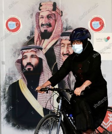 Stock Image of Amal, a Saudi cyclist member of women's brave cyclist team, rides her bicycle in front of a banner showing Saudi King Salman, right, his Crown Prince Mohammed bin Salman, left, and Saudi Arabia's founder late King Abdul Aziz Al Saud in Jiddah, Saudi Arabia . The brave cyclist team, which was formed in 2019 aiming to normalize the sport for women, organize a tour cycling ahead of International Women's Day