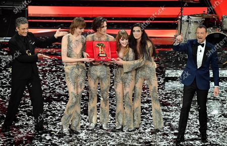 Stock Picture of Sanremo Festival host and artistic director, Amadeus (R), and Italian showman Rosario Fiorello (L) stand with Italian band Maneskin while they pose with the prize after winning the 71st Sanremo Italian Song Festival, Sanremo, Italy, 06 March 2021.