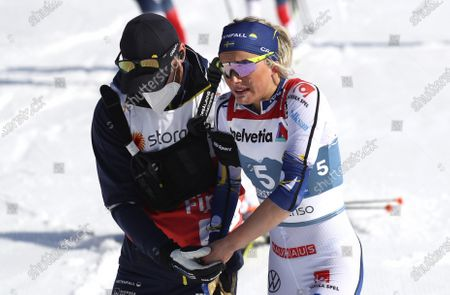 Sweden's Frida Karlsson is attended to at the finish line after being injured during the WSC Women's Mass Start 30km Classic cross country event at the FIS Nordic World Ski Championships in Oberstdorf, Germany