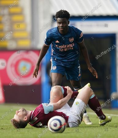 Stock Image of Burnley's Charlie Taylor reacts injured at the ground during the English Premier League soccer match between Burnley and Arsenal at Turf Moor stadium in Burnley, England