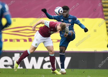 Arsenal's Thomas Partey and Burnley's Charlie Taylor challenge for the ball during the English Premier League soccer match between Burnley and Arsenal at Turf Moor stadium in Burnley, England