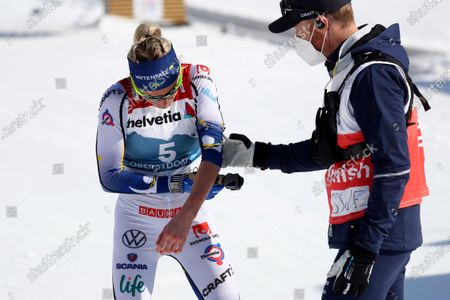 Sweden's Frida Karlsson holds her arm at the finish line during the WSC Women's Mass Start 30km Classic cross country event at the FIS Nordic World Ski Championships in Oberstdorf, Germany