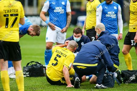 Michael Bostwick of Burton Albion (5) receives treatment after a clash of heads during the EFL Sky Bet League 1 match between Burton Albion and Peterborough United at the Pirelli Stadium, Burton upon Trent