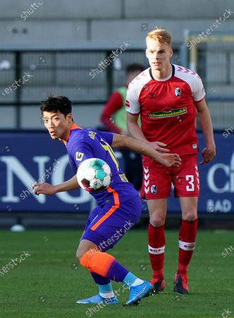 Hwang Hee-chan of RB Leipzig is watched by Philipp Lienhart of SC Freiburg (R) during the Bundesliga match between Sport-Club Freiburg and RB Leipzig at Schwarzwald-Stadionin Freiburg, Germany, 06 March 2021.
