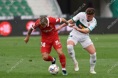 Stock Image of Papu Gomez of Sevilla and Raul Guti of Elche compete for the ball during the La Liga Santander match between Elche CF and Sevilla FC at Estadio Martinez Valero on March 6, 2021 in Elche, Spain.