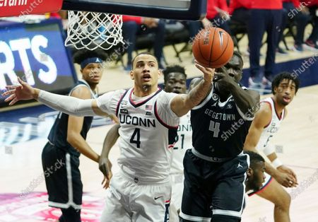 Connecticut guard Tyrese Martin (4) works for the rebound against Georgetown forward Chudier Bile (4) during the first half of an NCAA college basketball game, in Storrs, Conn