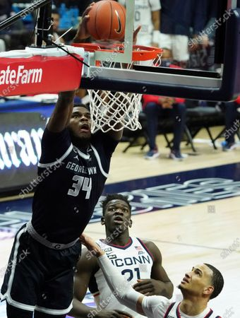Georgetown center Qudus Wahab (34) scores over Connecticut Huskies guard Tyrese Martin, lower right, during the second half of an NCAA college basketball game against Connecticut, in Storrs, Conn