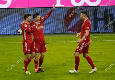 Bayern's Robert Lewandowski, center, celebrates with teammates Thomas Mueller and Niklas Suele, right, after scoring his side's fourth goal during the German Bundesliga soccer match between Bayern Munich and Borussia Dortmund at the Allianz Arena in Munich, Germany
