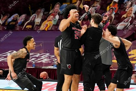 Rutgers' Jacob Young, left, and Ron Harper Jr. (24) celebrate with teammates after Rutgers beat Minnesota 77-70 in overtime of an NCAA college basketball game, in Minneapolis