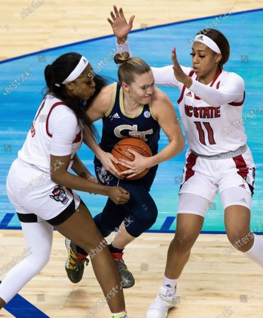 Stock Photo of Georgia Tech's Lotta-Maj Lahtinen (31) drives as North Carolina State's Jakia Brown-Turner (11) and North Carolina State's Jada Boyd (5) defend during an NCAA college basketball game in the semifinals of Atlantic Coast Conference tournament in Greensboro, N.C