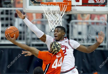 Ohio State forward E.J. Liddell, top, tries to block a shot by Illinois guard Adam Miller during the second half of an NCAA college basketball game in Columbus, Ohio