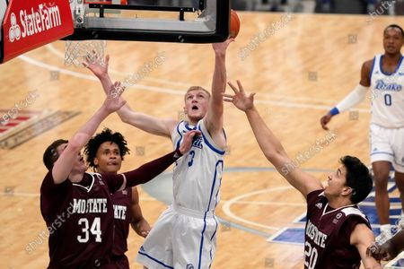 Stock Photo of Drake's Garrett Sturtz reaches for a rebound as Missouri State's Jared Ridder (34), Demarcus Sharp and Nic Tata (20) defend during the first half of an NCAA college basketball game in the semifinal round of the Missouri Valley Conference men's tournament, in St. Louis