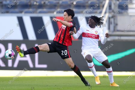 Makoto Hasebe (L) of Eintracht Frankfurt is challenged by Tanguy Coulibaly of VfB Stuttgart