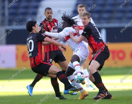 Tanguy Coulibaly (C) of VfB Stuttgart is challenged by Makoto Hasebe (L) of Eintracht Frankfurt and Martin Hinteregger (R) of Eintracht Frankfurt