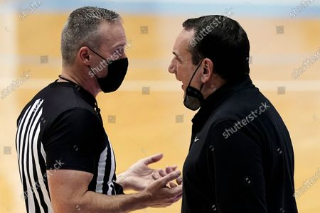 Duke coach Mike Krzyzewski, right, speaks with an official during the first half of the team's NCAA college basketball game against North Carolina in Chapel Hill, N.C