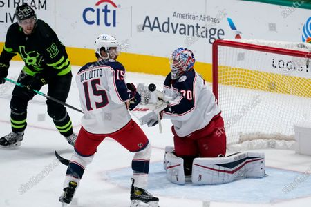 Dallas Stars center Radek Faksa (12) and Columbus Blue Jackets' Michael Del Zotto (15) look on as goaltender Joonas Korpisalo (70) attempts to glove an airborne puck in the first period of an NHL hockey game in Dallas