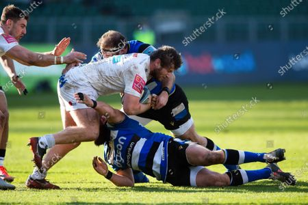 Alec Hepburn of Exeter Chiefs is double-tackled by Henry Thomas and Tom Dunn of Bath Rugby