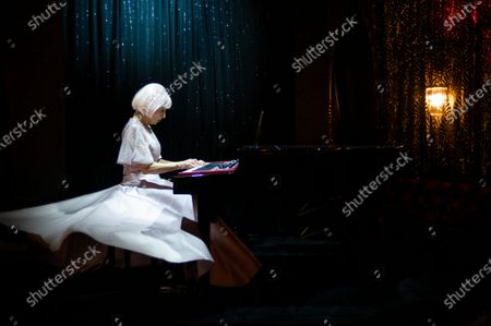 French artist Marie Beltrami plays piano during the shooting of a video presentation of French fashion designer Alexis Mabille Women's Fall/Winter 2021/2022 collection at Le Boeuf sur le Toit restaurant in Paris, France, 04 March 2021 (issued 07 March 2021). Amid the Covid19 pandemic, the Paris Fashion Week remains a purely digital event. Due to a curfew from 6pm daily and the ban on public gatherings, more than 90 brands had to adopt an online format to present their Fall/Winter collections. Mabille showcased his collection at the famed restaurant Le Boeuf sur le Toit, after redesigning its interior a year ago. Founded in 1922, this brasserie and music hall reopened on February 2020 after five months of renovations, but closed several days later because of the first national lockdown.