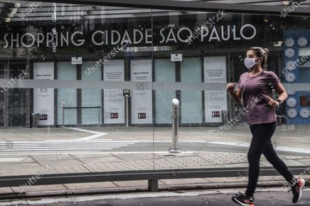A woman exercises in front of a closed mall in Sao Paulo, Brazil, March 6, 2021. The Governor of the Brazilian state of Sao Paulo Joao Doria announced on March 3 that starting on Saturday most store, bar and restaurant operations will be banned for two weeks, as a night curfew goes into effect, to prevent the collapse of the hospital system.