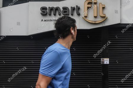 Stock Photo of A man exercises in front of a closed gym in Sao Paulo, Brazil, March 6, 2021. The Governor of the Brazilian state of Sao Paulo Joao Doria announced on March 3 that starting on Saturday most store, bar and restaurant operations will be banned for two weeks, as a night curfew goes into effect, to prevent the collapse of the hospital system.
