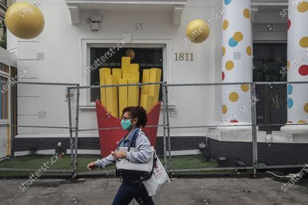 A woman walks past a fast food restaurant in Sao Paulo, Brazil, March 6, 2021. The Governor of the Brazilian state of Sao Paulo Joao Doria announced on March 3 that starting on Saturday most store, bar and restaurant operations will be banned for two weeks, as a night curfew goes into effect, to prevent the collapse of the hospital system.