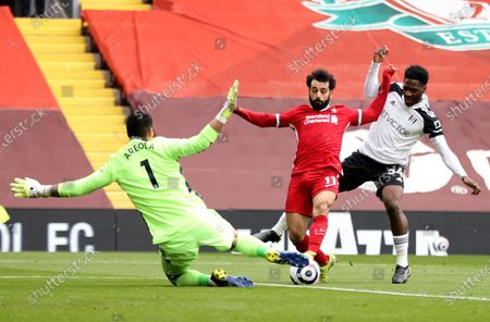 Mohamed Salah (C) of Liverpool in action against goalkepeer Alphonse Areola (L) of Fulham during the English Premier League soccer match between Liverpool FC and Fulham FC in Liverpool, Britain, 07 March 2021.