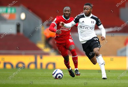 Liverpool's Naby Keita, left, and Fulham's Ademola Lookman challenge for the ball during the English Premier League soccer match between Liverpool and Fulham at Anfield stadium in Liverpool, England