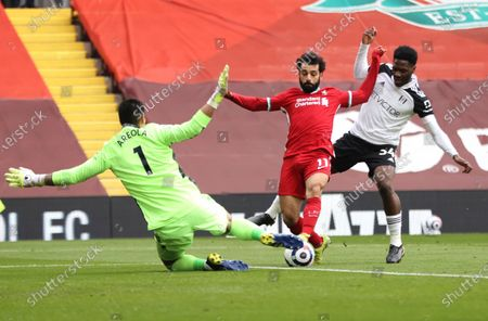 Liverpool's Mohamed Salah, centre, Fulham's goalkeeper Alphonse Areola, left, and Fulham's Ola Aina challenge for the ball during the English Premier League soccer match between Liverpool and Fulham at Anfield stadium in Liverpool, England