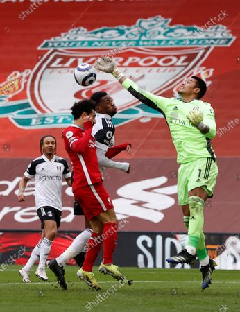 Fulham's goalkeeper Alphonse Areola punches the ball away under pressure from Liverpool's Mohamed Salah, left,during the English Premier League soccer match between Liverpool and Fulham at Anfield stadium in Liverpool, England