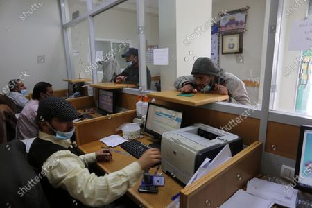 Palestinians wear protective face masks, as they wait to receive their financial aid, amid the coronavirus disease (COVID-19) outbreak, at the Post Office, in Dair Al Balah in the central of Gaza Strip, on March 7, 2021. HE Chairman of Qatar's Gaza Reconstruction Committee Ambassador Mohammed Al Emadi affirmed that since the beginning of its work in the field of Gaza reconstruction in 2012, starting with the USD 407 million grant of HH the Father Amir Sheikh Hamad Bin Khalifa Al-Thani, the Committee constituted a turning point in the field of development and reconstruction, and supervised hundreds of humanitarian projects with integrated plans to provide and meet the needs of the people of Gaza in various fields.