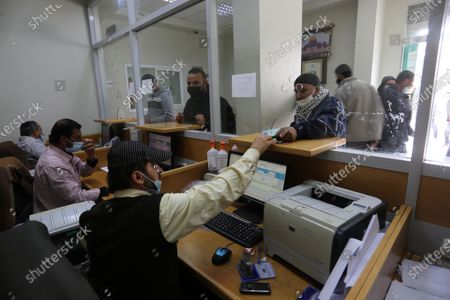 Editorial picture of Palestinians wear protective face masks, as they wait to receive their financial aid, amid the coronavirus disease (COVID-19) outbreak, at the Post Office, Dair Al Balah, Gaza Strip, Palestinian Territory - 07 Mar 2021