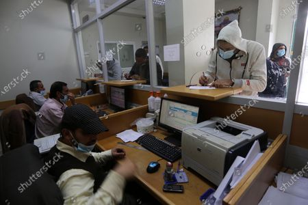 Editorial photo of Palestinians wear protective face masks, as they wait to receive their financial aid, amid the coronavirus disease (COVID-19) outbreak, at the Post Office, Dair Al Balah, Gaza Strip, Palestinian Territory - 07 Mar 2021
