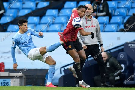 Manchester City's Joao Cancelo, left, vies for the ball with Manchester United's Anthony Martial during the English Premier League soccer match between Manchester City and Manchester United at the Etihad Stadium in Manchester, England