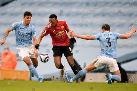 Manchester City's Ruben Dias, right, tackles Manchester United's Anthony Martial during the English Premier League soccer match between Manchester City and Manchester United at the Etihad Stadium in Manchester, England