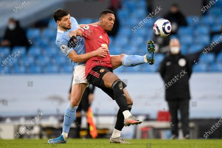 Manchester City's Ruben Dias, left, fights for the ball with Manchester United's Anthony Martial during the English Premier League soccer match between Manchester City and Manchester United at the Etihad Stadium in Manchester, England