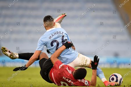 Manchester City's Riyad Mahrez fall down on top of Manchester United's Anthony Martial during the English Premier League soccer match between Manchester City and Manchester United at the Etihad Stadium in Manchester, England