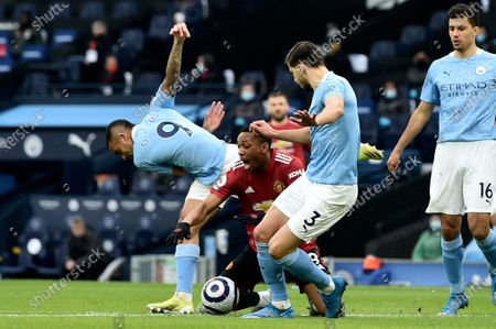 Manchester United's Anthony Martial, center, is fouled in the box to win a penalty during the English Premier League soccer match between Manchester City and Manchester United at the Etihad Stadium in Manchester, England