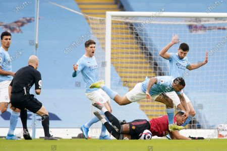 Manchester United's Anthony Martial, bottom, is fouled in the box to win a penalty during the English Premier League soccer match between Manchester City and Manchester United at the Etihad Stadium in Manchester, England
