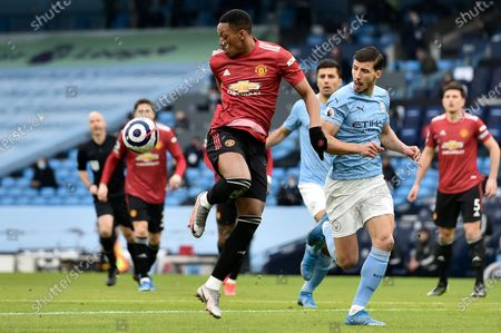 Manchester United's Anthony Martial, center left, controls the ball next to Manchester City's Ruben Dias during the English Premier League soccer match between Manchester City and Manchester United at the Etihad Stadium in Manchester, England