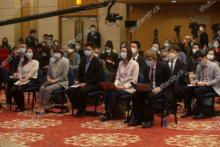 """Journalists wear face masks while attending Chinese State Councilor and Foreign Minister Wang Yi's virtual news conference during the country's parliamentary sessions.  Wang urged the U.S. to remove """"unreasonable"""" curbs on cooperation as soon as possible and work together on mutual interests like climate change.  Last week U.S. Joe Biden singled out China as a """"growing rivalry"""" and serious challenge facing the U.S.."""