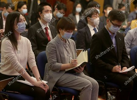 """Journalists wear face masks while attending Chinese State Councilor and Foreign Minister Wang Yi's virtual news conference during the country's parliamentary sessions in Beijing on Sunday, March 7, 2021.  Wang urged the U.S. to remove """"unreasonable"""" curbs on cooperation as soon as possible and work together on mutual interests like climate change.  Last week U.S. Joe Biden singled out China as a """"growing rivalry"""" and serious challenge facing the U.S.."""