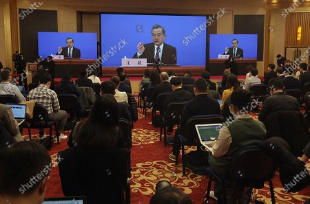 """Stock Photo of Chinese State Councilor and Foreign Minister Wang Yi speaks on a television screen as journalists wear masks (due to pandemic) at his annual news conference during the country's parliamentary sessions in Beijing.  Wang urged the U.S. to remove """"unreasonable"""" curbs on cooperation as soon as possible and work together on mutual interests like climate change.  Last week U.S. Joe Biden singled out China as a """"growing rivalry"""" and serious challenge facing the U.S.."""