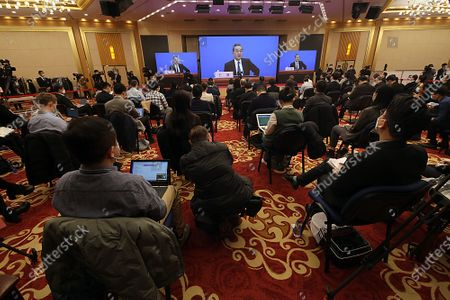 """Chinese State Councilor and Foreign Minister Wang Yi speaks on a television screen as journalists wear masks (due to pandemic) at his annual news conference during the country's parliamentary sessions in Beijing on Sunday, March 7, 2021.  Wang urged the U.S. to remove """"unreasonable"""" curbs on cooperation as soon as possible and work together on mutual interests like climate change.  Last week U.S. Joe Biden singled out China as a """"growing rivalry"""" and serious challenge facing the U.S.."""