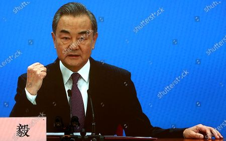 """Chinese State Councilor and Foreign Minister Wang Yi speaks on a television screen (due to pandemic) at his annual news conference during the country's parliamentary sessions.  Wang urged the U.S. to remove """"unreasonable"""" curbs on cooperation as soon as possible and work together on mutual interests like climate change.  Last week U.S. Joe Biden singled out China as a """"growing rivalry"""" and serious challenge facing the U.S.."""