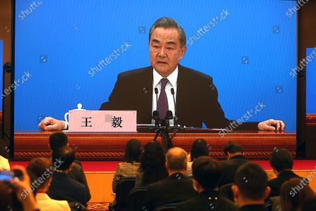 """Stock Picture of Chinese State Councilor and Foreign Minister Wang Yi speaks on a television screen (due to pandemic) at his annual news conference during the country's parliamentary sessions.  Wang urged the U.S. to remove """"unreasonable"""" curbs on cooperation as soon as possible and work together on mutual interests like climate change.  Last week U.S. Joe Biden singled out China as a """"growing rivalry"""" and serious challenge facing the U.S.."""