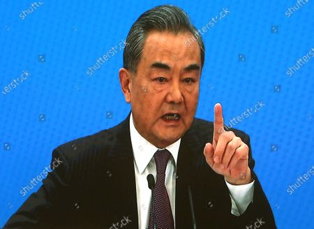 """Chinese State Councilor and Foreign Minister Wang Yi speaks on a television screen (due to pandemic) at his annual news conference during the country's parliamentary sessions in Beijing on Sunday, March 7, 2021.  Wang urged the U.S. to remove """"unreasonable"""" curbs on cooperation as soon as possible and work together on mutual interests like climate change.  Last week U.S. Joe Biden singled out China as a """"growing rivalry"""" and serious challenge facing the U.S.."""