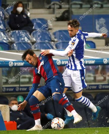 Real Sociedad's Belgian winger Adnan Januzaj (R) duels for the ball with Levante's defender Tono Garcia (L) during the Spanish LaLiga soccer match between Real Sociedad and Levante UD at Reale Arena stadium in San Sebastian, Basque Country, Spain, 07 March 2021.
